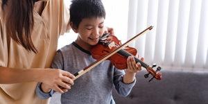 はじめてのバイオリンレッスンを受ける小学生の男の子